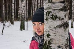 Bild av den nätta kvinnablicken ut bakifrån ett träd fotografering för bildbyråer