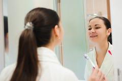 Bild av den nätta kvinnlign som framme borstar hennes tänder av spegeln arkivfoton