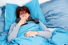 Bild av den sjuka kvinnan som ligger på säng royaltyfri bild