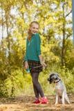 Bild av den skämtsamma lilla flickan som poserar med valpen Royaltyfri Foto