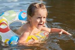 Bild av den skrämda söta öppningsmunnen och ögon för liten unge brett med skräck och att simma med gummicirkeln som skriker för h arkivbild