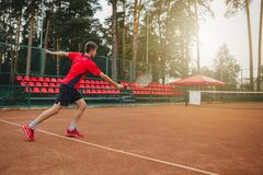 Bild av den stiliga unga mannen på tennisbanan leka tennis för man Man som kastar tennisbollen Härligt skogområde som royaltyfria bilder
