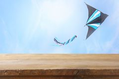 Bild av den tomma lantliga tabellen framme av det färgrika drakeflyget i den blåa himlen till och med molnen För produktskärmpres Arkivfoto