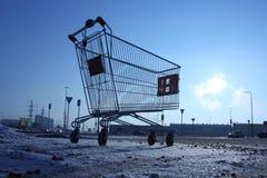 Bild av den tomma shoppingvagnen på tom parkering nära enormt lager Arkivbilder
