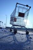 Bild av den tomma shoppingvagnen på tom parkering nära enormt lager Arkivfoton