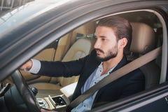Bild av den trevliga och säkra affärsmannen som sitter i lyxig bil Han ser rättfram Mannen poserar Han har säkerhetsbältet fotografering för bildbyråer