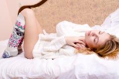 Bild av den unga blonda kvinnan för söt sexig glamour som kopplar av att ligga på henne tillbaka i vit säng i en tröja och sockor Arkivbild