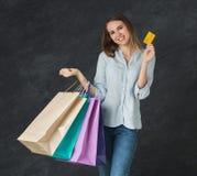 Bild av den unga blonda kvinnan med shoppingpåsar fotografering för bildbyråer