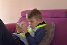Bild av den unga gulliga pojken som spelar lekar på mobiltelefonen som är slö på soffan arkivfoto