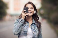 Bild av den unga lyckliga kvinnan, lyssnande musik och hagyckel Arkivfoton