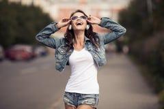Bild av den unga lyckliga kvinnan, lyssnande musik och hagyckel arkivfoto