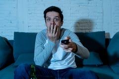 Bild av den unga mannen som ser förskräckt sammanträde på hållande ögonen på TV för soffa på natten I mänskligt sinnesr royaltyfri foto