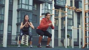 Bild av den unga sportiga man- och kvinna20-tal i träningsoveraller som gör genomkörare och tillsammans squatting stock video