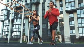 Bild av den unga sportiga man- och kvinna20-tal i träningsoveraller som gör genomkörare och tillsammans squatting arkivfilmer