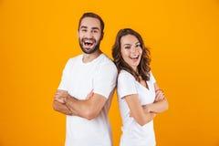Bild av den ungdomarmannen och kvinnan i grundläggande kläder som ler, medan stå tillsammans isolerat över gul bakgrund royaltyfri fotografi