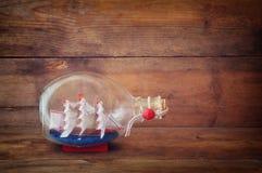 Bild av det dekorativa fartyget i flaskan på trätabellen Nautiskt begrepp retro filtrerad bild arkivfoton
