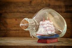 Bild av det dekorativa fartyget i flaskan på trätabellen Nautiskt begrepp retro filtrerad bild royaltyfri foto