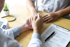 Bild av doktorn som rymmer patients hand för att uppmuntra och att tala med tålmodigt bifall och service royaltyfria foton