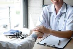 Bild av doktorn som rymmer patients hand f?r att uppmuntra och att tala med t?lmodigt bifall och service royaltyfria foton