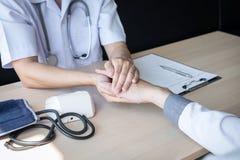 Bild av doktorn som rymmer patients hand f?r att uppmuntra och att tala med t?lmodigt bifall och service arkivbild
