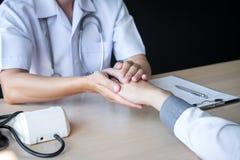 Bild av doktorn som rymmer patients hand f?r att uppmuntra och att tala med t?lmodigt bifall och service arkivbilder