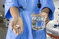 Bild av doktorshänder som ger vita preventivpillerar royaltyfri fotografi
