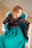Bild av elegant flickasammanträde i retro stilfåtölj Redhaired lockig barnmodell Royaltyfria Bilder