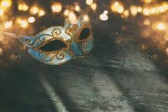 Bild av eleganta blått och guld- venetian, mardigrasmaskering över svart bakgrund arkivfoto