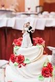 Bild av en härlig bröllopstårta på bröllopmottagandet modeller av nygifta personerna på den bästa raden Arkivbilder