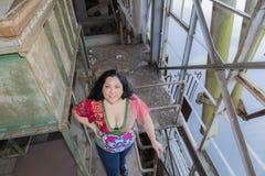 Bild av en härlig kvinna i en mångfärgad blus och jeans royaltyfri fotografi