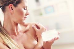 Bild av en hållande lotion för passformkvinna över hennes kropp royaltyfria foton