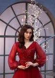 Bild av en julhäxa, en ljuv röd klänning som smyckas med blommor, och muffar, en flicka med varmt krabbt hår, ett nytt royaltyfri foto