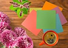 Bild av en kopp kaffe, blommor, papper fotografering för bildbyråer