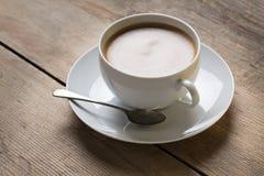 Bild av en kopp kaffe på en suacer med en gammal tappningsked och en vaniljkaka som förläggas på en trätabellöverkant Arkivbilder