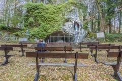 Bild av en kvinna som sitter på en bänk som ber utomhus till oskulden av Lourdes royaltyfria bilder