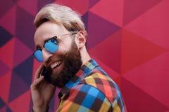 Bild av en lycklig ung man i solglas?gon som rymmer en mobiltelefon, p? en f?rgrik bakgrund med sexh?rningsformen royaltyfria bilder