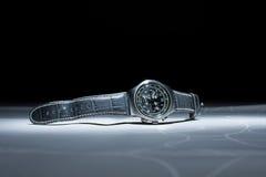 Bild av en mans armbandsur med läderremmen på den vita tabellen Royaltyfri Bild
