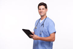 Bild av en stilig ung sjukskötare som använder den digitala minnestavlan Arkivbild