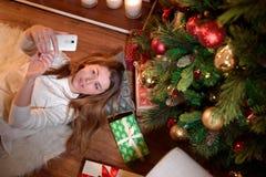 Bild av en ung kvinna som tar en gullig selfie royaltyfri bild