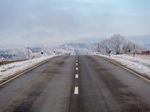 Bild av en väg i ett vinterlandskap fotografering för bildbyråer