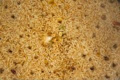 Bild av ett aptitretande kokt ris med ett huvud av vitlök och hål från bubblorna av ånga Arkivbild
