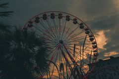 Bild av ett ferrishjul på en molnig dag under solnedgång royaltyfri fotografi