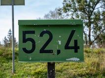 Bild av ett gammalt tecken med nummer på det arkivbilder