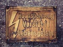 Bild av ett gammalt varnande tecken med pråliga och tyska ord Hochspannung Vorsicht Lebensgefahr, som betyder hög fara royaltyfri foto