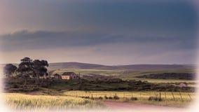 Bild av ett naturligt landskap i mjuka färger med ett hus, träd, en mörk himmel, gräsplanfält med en häck och vägen med en vit vi Arkivfoton