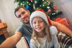 Bild av fadern och dottern som sitter på golv De ser raka och leendet Den unga mannen rymmer kameran De tar selfie royaltyfri bild