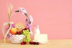 Bild av frukter och ost i dekorativ korg med blommor över trätabellen Symboler av judisk ferie - Shavuot arkivbilder