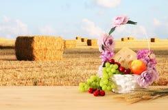 Bild av frukter och ost i dekorativ korg med blommor över trätabellen Symboler av judisk ferie - Shavuot arkivfoto