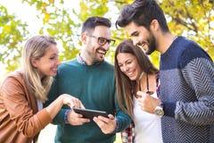Bild av fyra lyckliga le unga vänner som utomhus går Arkivbilder