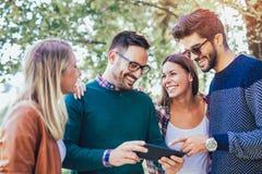 Bild av fyra lyckliga le unga vänner som utomhus går Royaltyfri Fotografi